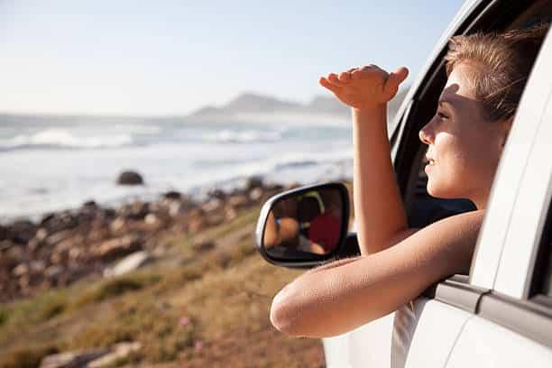 Femme dans une voiture qui regarde le paysage par la fenêtre