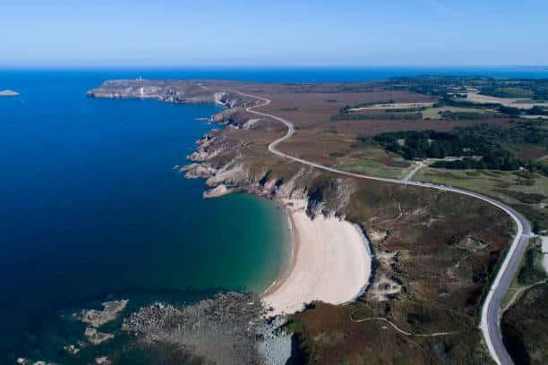 Vue aérienne du littoral breton avec une route qui serpente le long des falaises