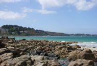 Vue de la mer depuis une plage bordée par des rochers à Perros-Guirec